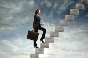 Mujer-con-un-maletin-subiendo-una-escalera-con-el-cielo-de-fondo